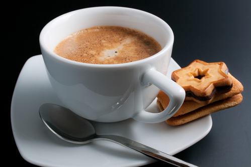 White porcelain cup of freshly brewed coffee close-up arranged with two sandwich-biscuits spoon and plate on dark background