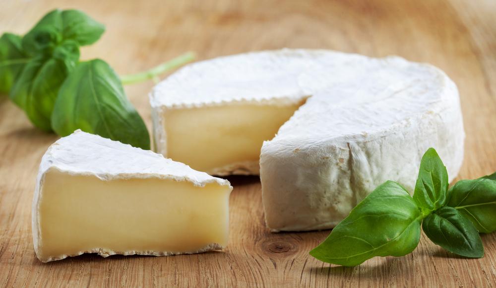 Camambert cheese on wooden cutting board