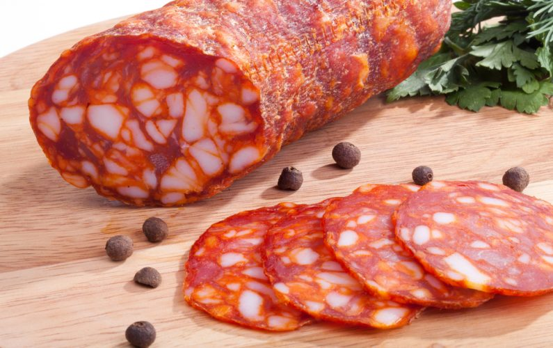 Chorizo ​​sausage pepperoni with herbs and pepper on the board