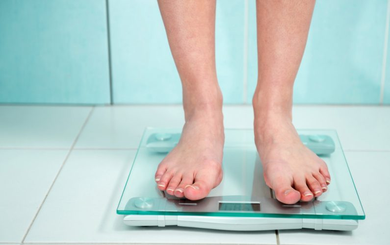 close up of woman standing on a scale in bathroom