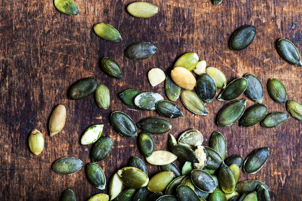 Pumpkin seeds on table - 7 Foods High In Magnesium