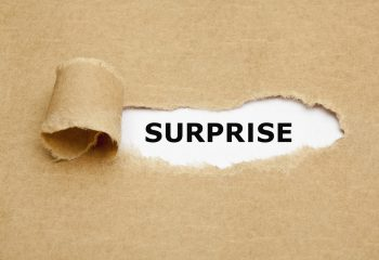 The word Surprise appearing behind torn brown paper.