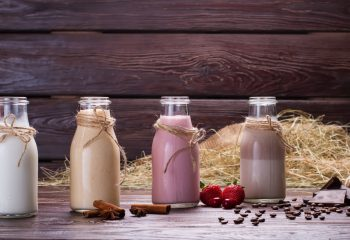 Different flavoured meal replacement shakes on the background of hay and sackcloth.