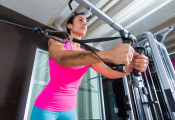 A woman doing standing cable crossover fly pulley flies workout at gym