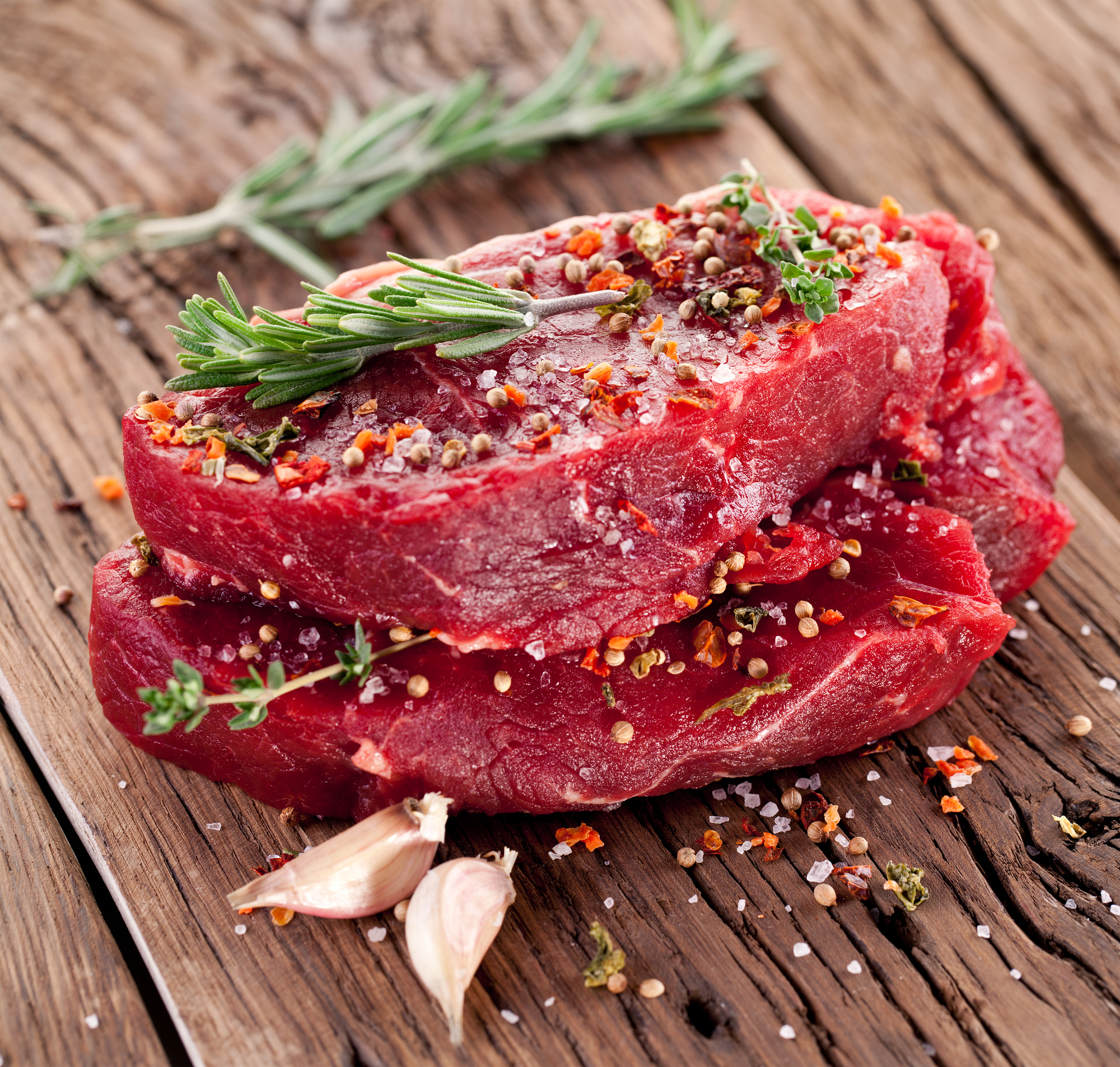 Raw beef steaks on a table top with sprig of rosemary and garlic